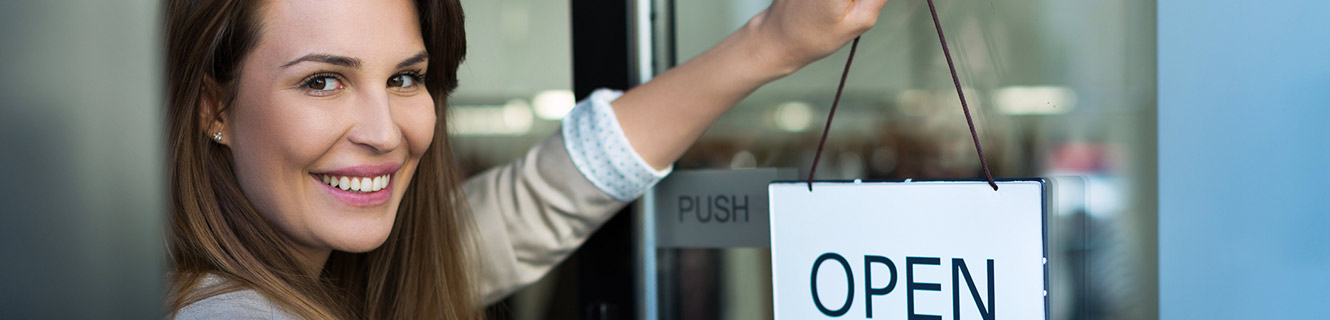Image of a business woman placing an 'Open' sign on the door.