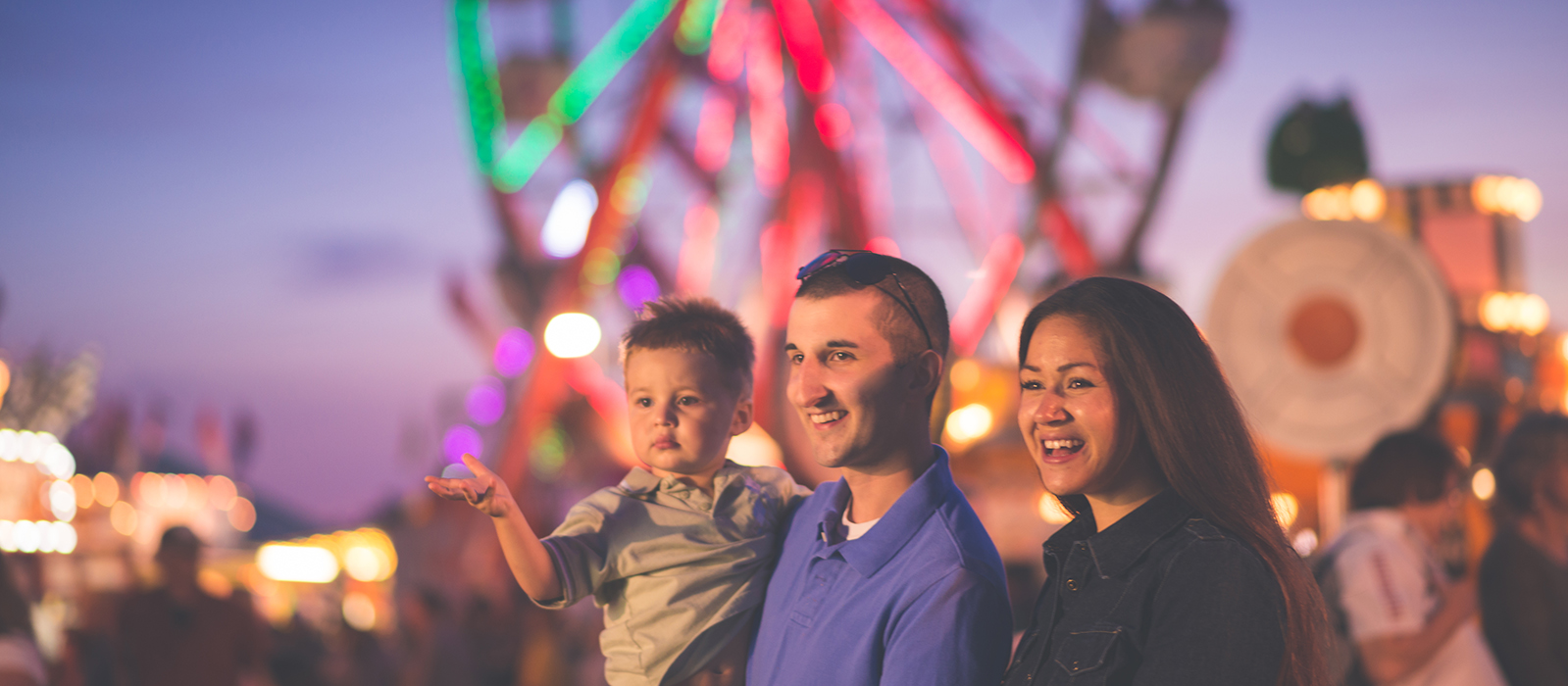 Family at a fair in the evening with a ferris wheel lit up behind them.