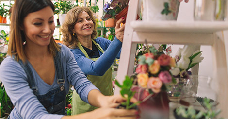Two florists working together in a small flower shop.
