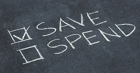 "A chalkboard with ""save"" and ""spend"" written on it. The word ""save"" has a checkmark next to it."
