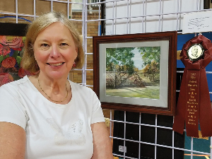 Artist Sandy Hall with one her paintings