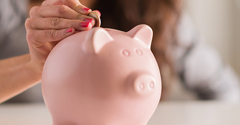 A woman placing a coin in a pink piggy bank.