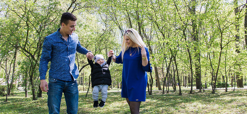 Young couple in a wooded area in the Spring swinging their toddler between them