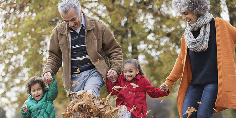 Older man & woman playing in autumn leaves with two children.